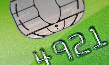 Image is a macro close-up of a green credit card, with silver numbers 4921